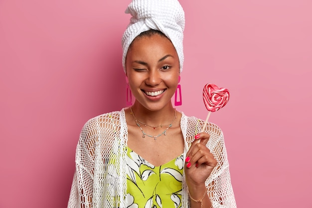 Happy cheerful woman feels refreshed after taking shower, wears wrapped towel on head, has healthy skin, white teeth, winks eye and smiles broadly, holds lollipop, isolated on pink wall