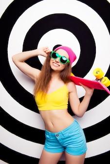 ピンクのスケートボードを保持しているメガネで幸せな陽気な女性