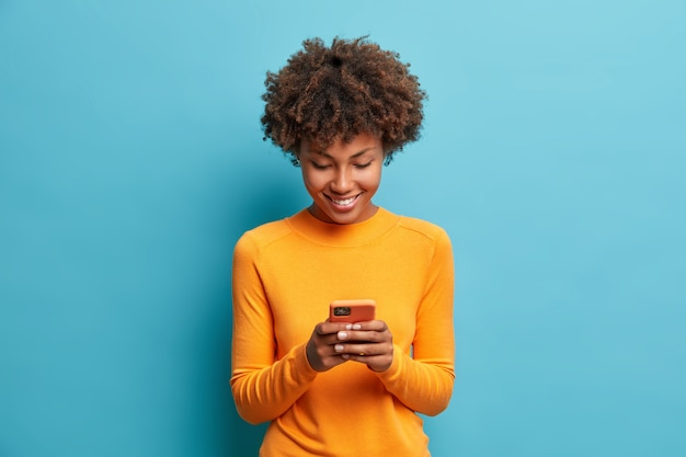 Happy cheerful woman looks at screen of smart phone enjoys online chatting types text message surfs social networks dressed casually poses against blue wall