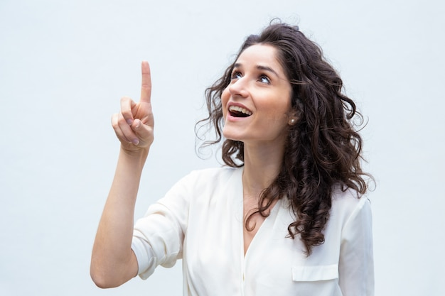 Happy cheerful woman pointing finger up