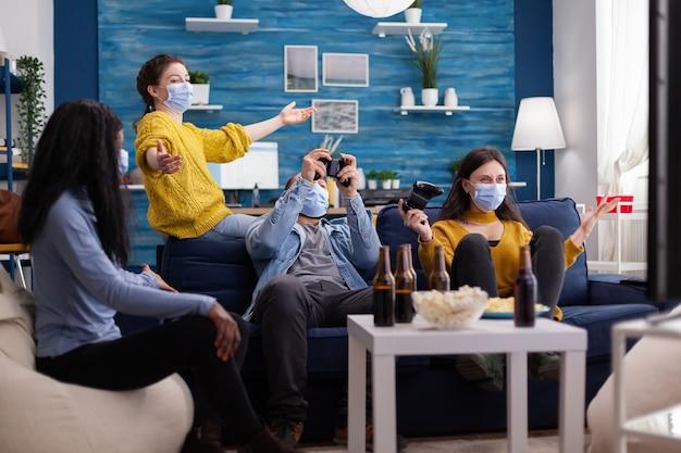 전 세계적으로 유행하는 코로나바이러스 확산을 방지하기 위해 안면 마스크를 쓰고 집 거실에서 다민족 친구들과 게임 경쟁에서 승리한 후 행복한 쾌활한 여성이 비명을 지릅니다.