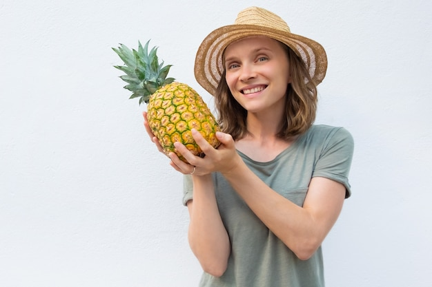 Happy cheerful woman in summer hat showing whole pineapple fruit