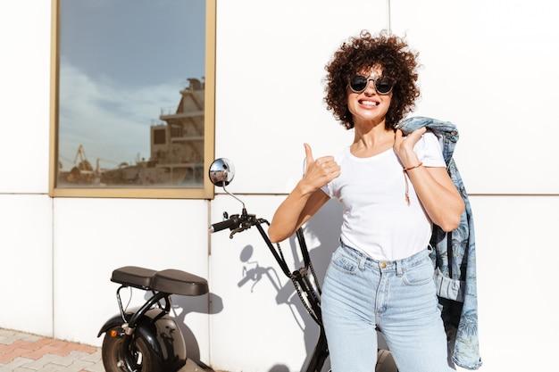 Donna allegra felice nella posa degli occhiali da sole