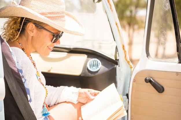 幸せな陽気な女性は、バンの読書の中で旅行します。晴れた明るい休暇の日の紙の本