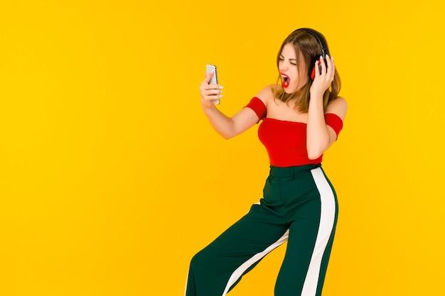 Счастливая веселая женщина в беспроводных наушниках слушает музыку со смартфона