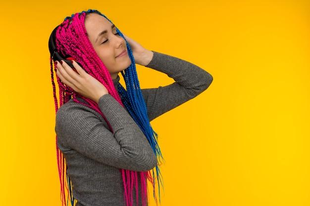 音楽を聴いてワイヤレスヘッドフォンを身に着けている三つ編みとそばかすの幸せな陽気な女性