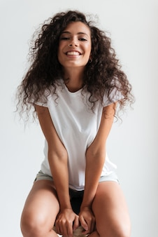 Happy cheerful woman with curly hair sitting on a chair
