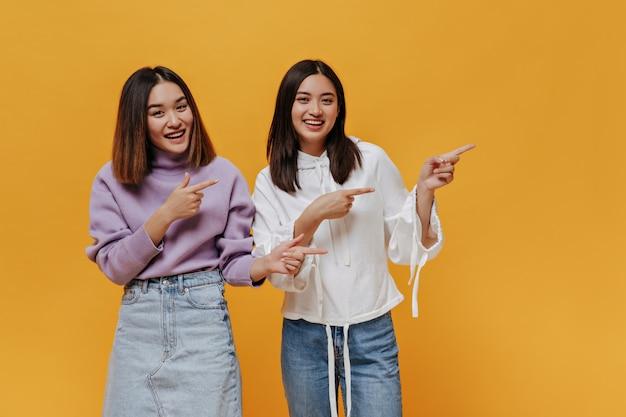 幸せな陽気な女性はオレンジ色の壁にテキストの場所を指しています