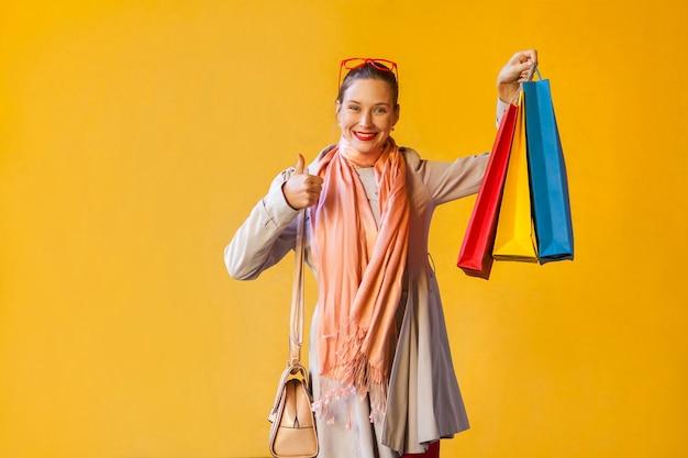 Счастливая жизнерадостная молодая взрослая девушка с веснушками, пучком волос, глядя в камеру, поднимает палец вверх, держит много сумок для покупок, радостно смотрит, наслаждается хорошим днем и свободным временем в помещении. студийный снимок