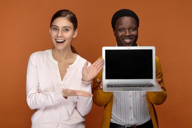 Felice allegro giovane venditore afroamericano e il suo collega dall'aspetto amichevole eccitato in piedi uno accanto all'altro, pubblicità nuovissimo gadget elettronico portatile generico e sorridente