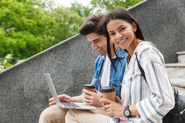 Счастливые веселые молодые удивительные любящие пары деловых людей коллеги на открытом воздухе снаружи на шагах, используя портативный компьютер, пить кофе.