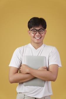 행복 한 쾌활 한 젊은 아시아 남자 괴상 한 학생 부담없이 고립 된 노트북 컴퓨터를 들고 안경을 쓰고 옷을 입고