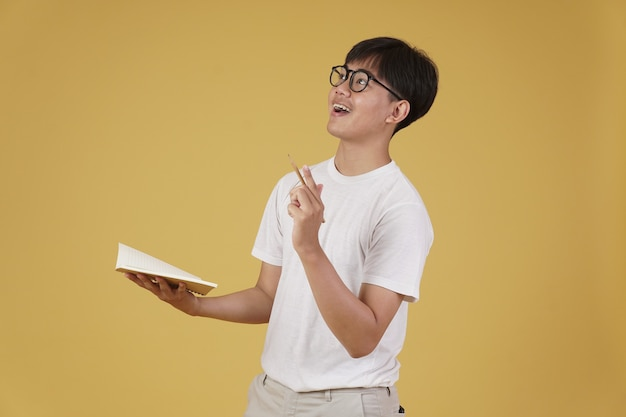 Happy cheerful young asian man student dressed casually wearing eyeglasses pointing finger up having idea isolated