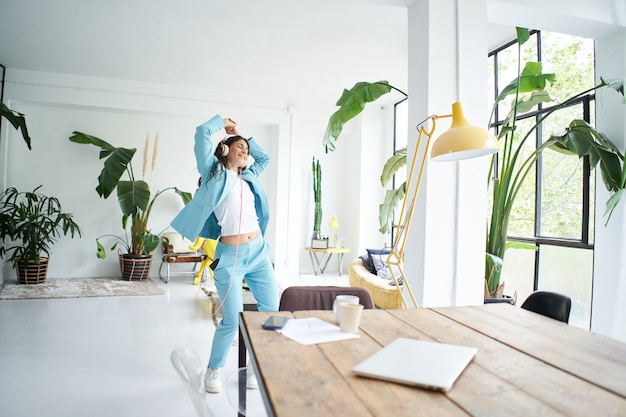 ホームオフィスで勝利のダンスを踊るフォーマルなスーツを着た幸せで陽気な若い魅力的なビジネス女性...