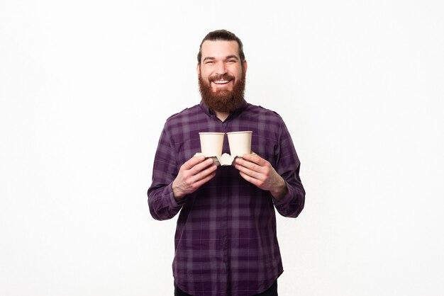 行くために2杯のコーヒーを持っている幸せな陽気な若いひげを生やした男