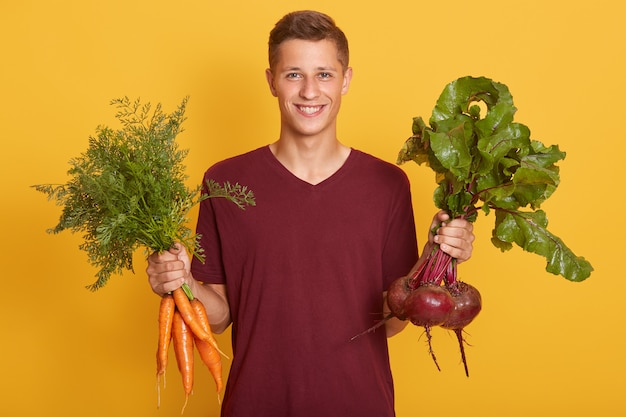 Happy cheerful young blond man holding healthy vegetables for salad.