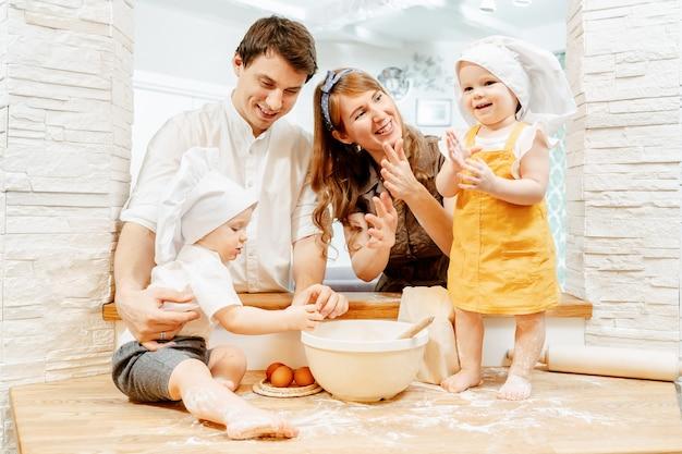 幸せな陽気な若い白人家族のお母さんお父さんと双子の男の子