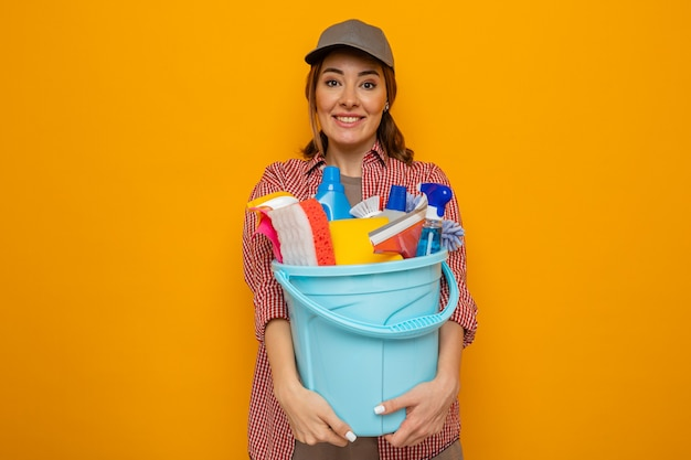 Happy and cheerful young cleaning woman in plaid shirt and cap holding bucket with cleaning tools looking at camera smiling broadly standing over orange background
