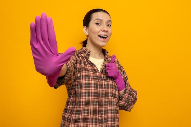 Felice e allegra giovane donna delle pulizie in camicia a quadri in guanti di gomma che mostra il quinto con il palmo, alto cinque in piedi sull'arancione