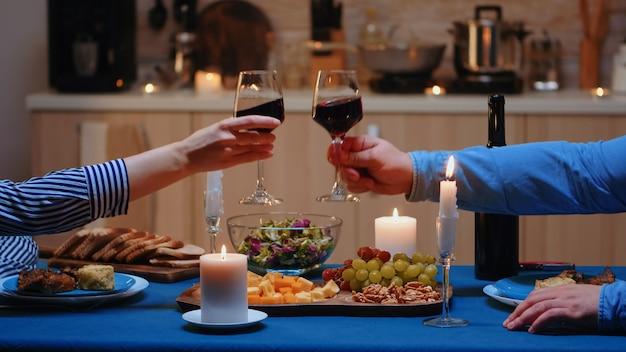 행복한 젊은 부부가 함께 식사를 하고 아늑한 주방에서 적포도주 잔을 부딪칩니다. 행복한 백인 연인들이 식사를 즐기고 식당에서 기념일을 축하합니다.