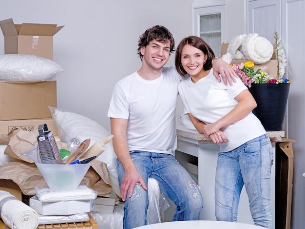 新しいアパートで抱きしめる幸せな陽気な若いカップル