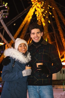 Happy cheerful young couple having fun at the ice skating park at night, holding cups of takeaway coffee