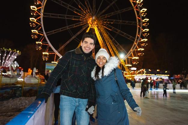 Happy cheerful young couple having fun at the ice skating park at night
