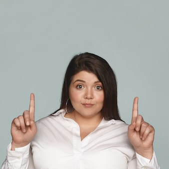 Happy cheerful young dark haired female with chubby cheeks and curvy large body staring with excited look, pointing both fore fingers upwards