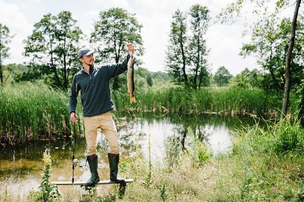 幸せな陽気な若い漁師は、橋、湖の近くの桟橋に大きな魚のパイクを保持します。