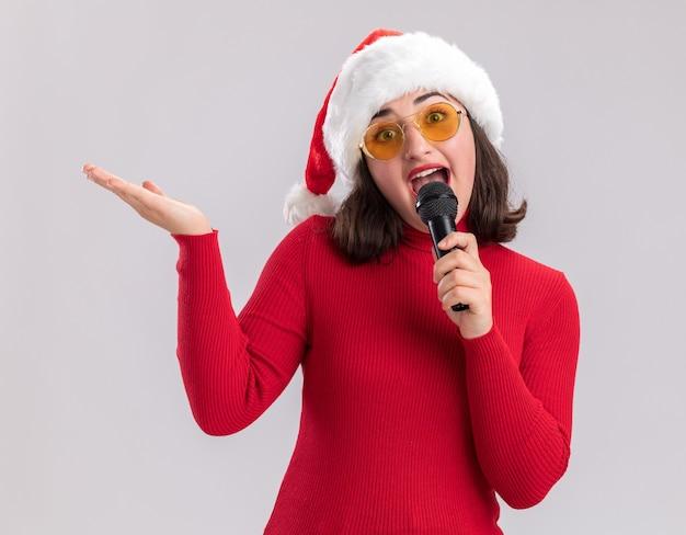 Ragazza felice e allegra in maglione rosso e cappello da babbo natale con gli occhiali tenendo il microfono guardando la fotocamera sorridente con il braccio alzato in piedi su sfondo bianco