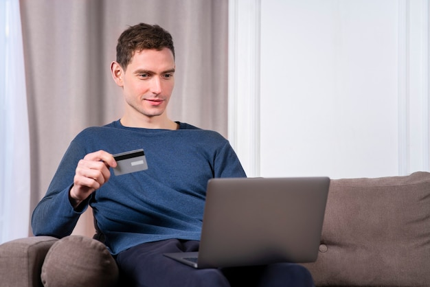 Happy cheerful young guy, handsome man with credit bank card paying online in shop, enter