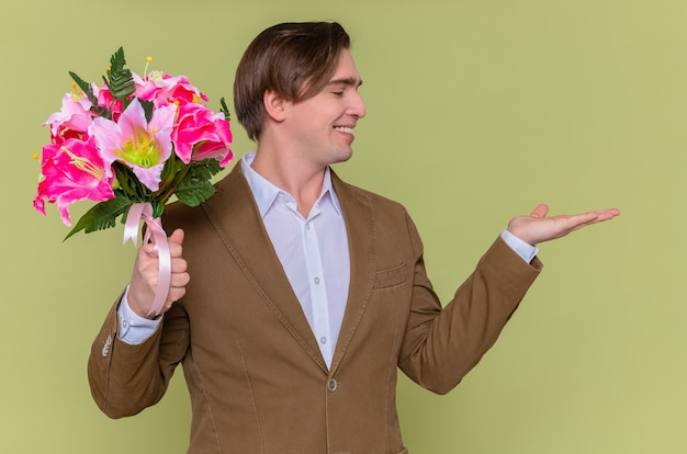Happy and cheerful young man holding bouquet of flowers looking aside smiling cheerfully presenting with arm going to congratulate with international womens day march concept