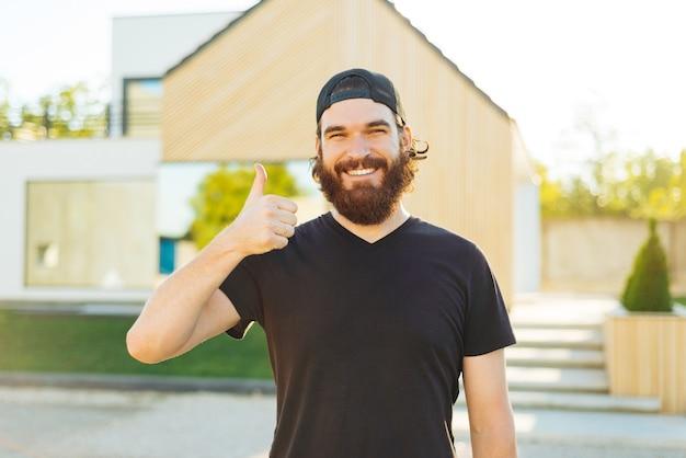 親指を立てて、彼のモダンな家の前に立っている幸せな陽気な若い男
