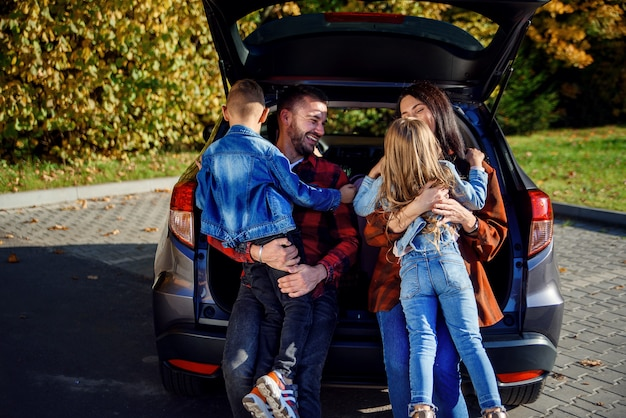 Happy cheerful young parents sitting in the car's trunk and hug their happy kids