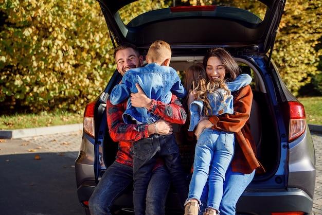 車のトランクに座っている幸せな陽気な若い親は、走っている幸せな子供たちを抱き締めます。