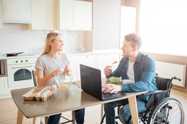 Happy cheerful young student with disability and inclusiveness eating salad and studying. he look at woman and smile. she cooks. happy couple sit together in kitchen