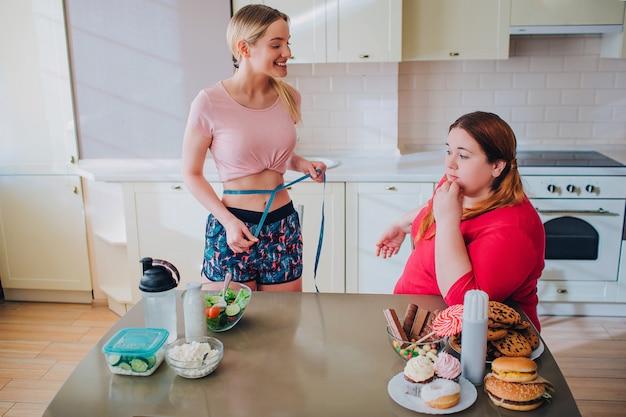 幸せな陽気な若いしっかりした造りの女性はプラスサイズモデルを見てください。彼女の腰の周りの青い柔らかいテープ。思いやりのある太りすぎのモデルが彼女を見ます。テーブルの上の健康で不健康な食事。