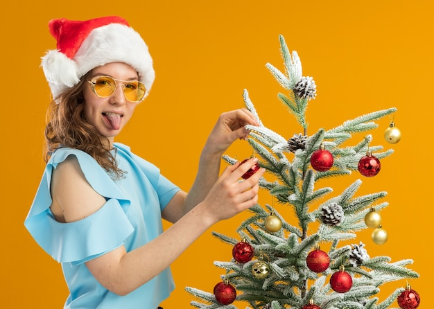 Happy and cheerful young woman in blue top and santa hat wearing yellow glasses decorating christmas tree sticking out tongue standing over orange background