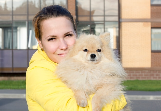 Happy cheerful young woman holding pomeranian spitz dog on her hands, looking at camera. girl is walking with her small fluffy cute puppy, autumn sunny cold cool day. people love their pet concept.