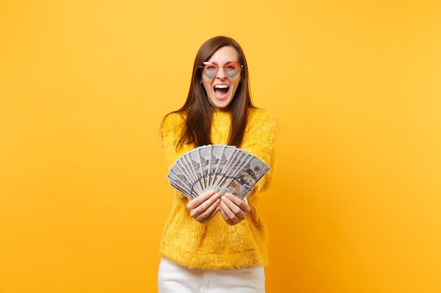 Счастливая жизнерадостная молодая женщина в очках сердца кричала, держа пачку много долларов, наличные деньги, изолированные на ярко-желтом фоне. люди искренние эмоции, концепция образа жизни. рекламная площадка.