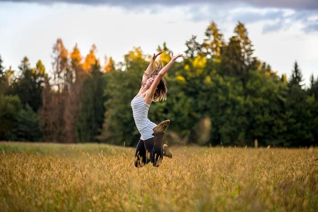 高い草と黄金の牧草地の真ん中で空中にジャンプする幸せな陽気な若い女性。人生、幸福、ライフスピリットを楽しむことの概念。