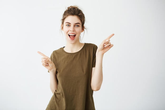 Happy cheerful young woman smiling with opened mouth pointing fingers in side.