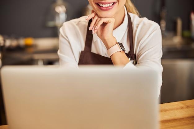 노트북에 실내에 서 있는 행복 한 쾌활 한 젊은 여자