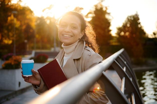 가을 공원에서 파란색 테이크아웃 종이 머그컵과 손 책을 들고 행복한 쾌활한 젊은 여성은 노란 황금빛 잎의 배경에 떨어지는 햇빛과 함께 카메라를 보며 미소를 짓습니다. 가을