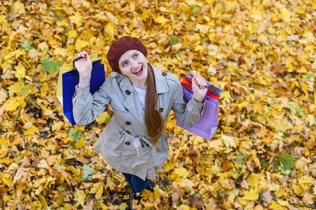 Счастливая веселая молодая женщина с покупками в руках гуляет в осеннем парке