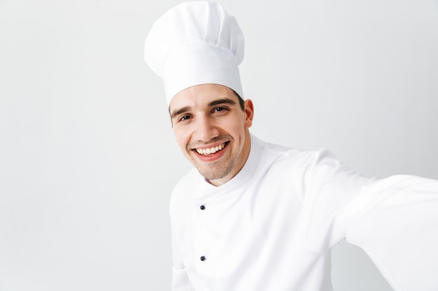 Happy chef cook wearing uniform standing isolated over white wall, taking a selfie