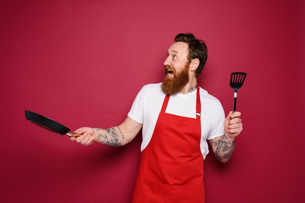행복한 요리사가 빨간색으로 새로운 창의적인 레시피를 요리합니다.