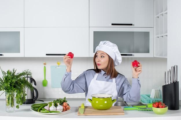 Chef felice e verdure fresche con attrezzatura da cucina e pomodori in mano nella cucina bianca
