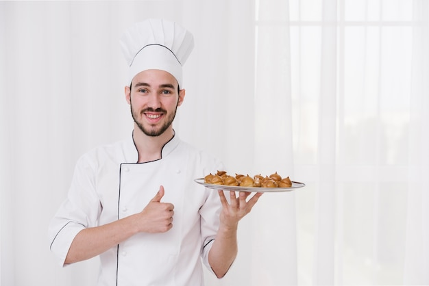 Happy chef holding plate with flamed meringue