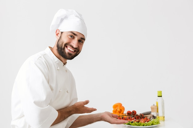 Happy chef man in cook hat smiling and posing with vegetable salad at work isolated over white wall